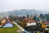 Austria. View from the window of the going train on the foothills of the Alps in the foggy autumn af