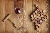Red wine glass, corkscrew and grape shaped corks on wooden table background