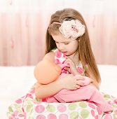 Cute Smiling Little Girl Playing With A Doll