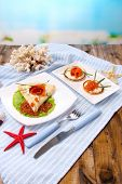 Pancakes with red caviar, salmon and mayo, green onion, on plate, on color napkin, on wooden  table,