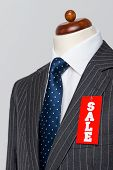 Side view Mens grey wool pinstripe suit jacket with blue tie and white shirt on a tailors dummy, sal