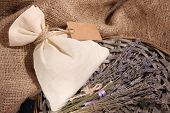 stock photo of sachets  - Textile sachet pouch with dried lavender flowers on wooden table - JPG