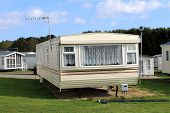 Scenic view of trailer on caravan park in summer with cloudscape background.