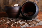 Golden coins in ceramic pots, on wooden background