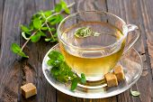 stock photo of stimulation  - Mint tea in a transparent glass cup and fresh leaves on a wooden table - JPG