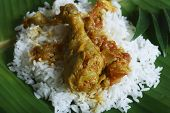 stock photo of tamil  - Top view of Kozhambu served with rice. This is a spicy chicken curry from Tamil Nadu.