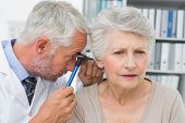 Close-up of a male doctor examining senior patient's ear at the medical office