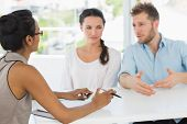 Therapist speaking with couple sitting at desk in therapists office
