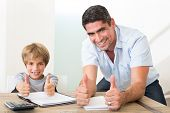 Portrait of happy father and son gesturing thumbs up while doing homework at table