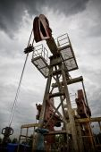 picture of nonrenewable  - Oil rig pump dramaticly underexposed against contrast cloudy sky low angle view - JPG