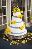four tiered wedding cake with blue stripes and yellow flowers