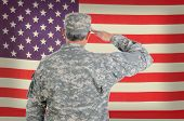 Closeup of a middle aged American soldier in fatigues saluting an old and weathered flag. The flag f