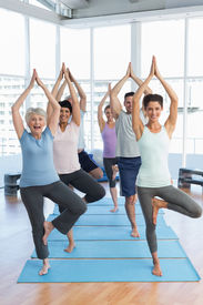 stock photo of senior class  - Portrait of a smiling trainer with class standing in tree pose at yoga class - JPG