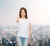 advertising, childhood, gesture and people concept - smiling little girl in white blank t-shirt showing thumbs up over city background