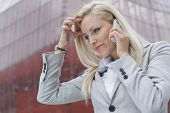 Close-up of shocked businesswoman communicating on cell phone against office building