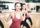 fitness, sport, training, gym and lifestyle concept - smiling trainer in front of the group of peopl