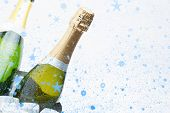 Snow falling against two champagne bottles chilling on ice