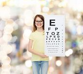 vision, health and people concept - smiling little girl wearing eyeglasses with eye checking chart