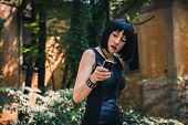 Pretty Goth Girl Using Phone In A City Park
