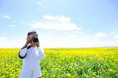 woman photographer taking photo in cole flower field