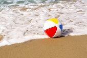 A colorful, summertime beach ball washes up to a sandy beach while being pushed by the ocean??s gent