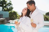 Cheerful romantic young couple with champagne flutes by swimming pool