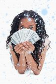 A woman is holding American dollars up to her face against snow falling