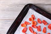 Sun dried tomatoes on drying tray, on wooden background