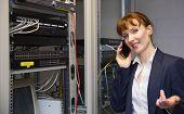 Pretty computer technician talking on phone beside open server in large data center