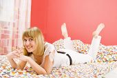 stock photo of teenage girl  - Beautiful blonde girl lying on the bed - JPG