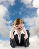 Redhead businesswoman with head in hands against blue sky with white clouds