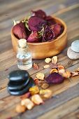 Dry rosebuds, spa stones and aromatic oil on wooden surface