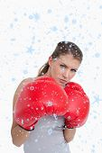 Portrait of a woman boxing against snow falling