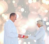 Couple exchanging gift against white glowing dots on grey