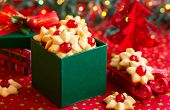 Christmas cookies with red candied cherries in the green gift box