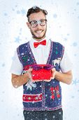 Geeky hipster offering christmas gift against snow falling