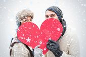 Attractive young couple in warm clothes holding red heart against snow falling