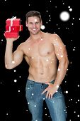 Muscular man holding pile of presents in blue jeans against snow falling