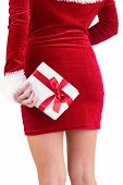 Sexy santa girl holding gift behind back on white background