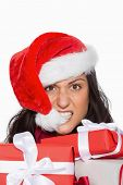 Irritated woman with christmas presents on white background