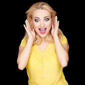 Beautiful blond woman with a surprised excited expression holding her hands to her cheeks with her e
