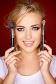 Gorgeous beautiful young blond woman holding two cosmetic brushes in her hands on either side of her face as she smiles at the camera