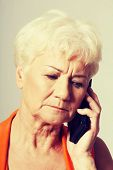 An old lady talking through phone.She is receiving bad news. Over grey background.
