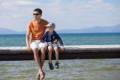 stock photo of dock a lake  - cheerful family of two sitting at the dock during vacation at lake tahoe california usa - JPG