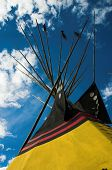 stock photo of american indian  - Indian teepee framed by blue skies and clouds - JPG