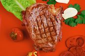 bbq : beef (pork) steak garnished with green lettuce and red chili hot pepper on red plate isolated