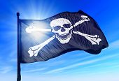 stock photo of skull crossbones flag  - Pirate skull and crossbones flag waving on the wind - JPG