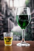 Glass with green cocktail and yellow shot