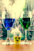 Glasses with green and blue cocktail yellow shot
