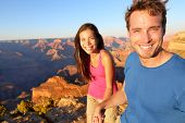 Lifestyle couple hiking in Grand Canyon. Hikers image of happy young people on hike holding hands on